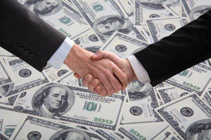 Businessmen shaking hands over money