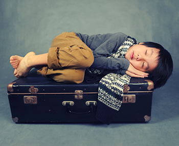 Child sleeping on suitcase (Source: Shutterstock)