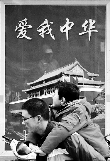 "Pedestrians pass by ""Love our China"" cigarette billboard (from Shenzhen Daily)"