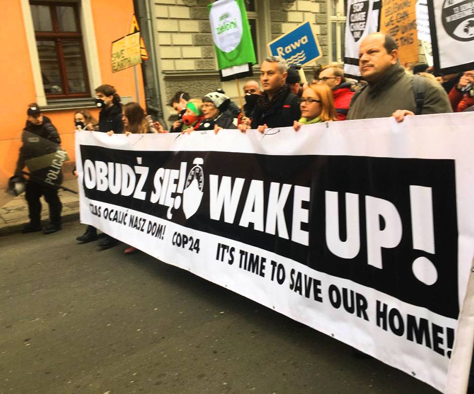 "COP 24 ""March for Climate"" participants carrying a ""Wake Up!"" banner."