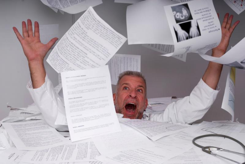 Doctor drowning in paperwork
