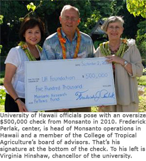 University of Hawaii officials pose with an oversize $500,000 check from Monsanto in 2010